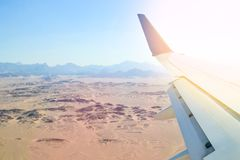 Landing and turning the plane over the desert. View from the porthole on the wing of the plane with the flaps down during landing at the Egyptian airport stock photography