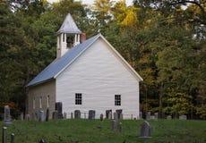 Landkirche und -Friedhof umgeben durch Bäume und grünes Gras lizenzfreie stockbilder