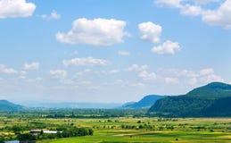 Landlandschaft im Gebirgstal mit Ackerland auf blauem Himmel Lizenzfreie Stockfotografie
