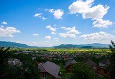 Landlandschaft im Gebirgstal mit Häusern auf blauem Himmel Lizenzfreie Stockfotos