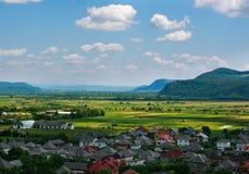 Landlandschaft im Gebirgstal mit Häusern auf blauem Himmel Stockbild