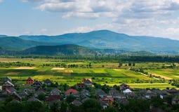 Landlandschaft im Gebirgstal mit Häusern auf blauem Himmel Lizenzfreie Stockbilder