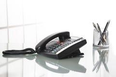 Landliine black phone on an office desk. Royalty Free Stock Photos