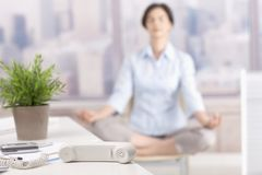 Landline phone put aside in skyscraper office. Woman meditating in background Stock Photos