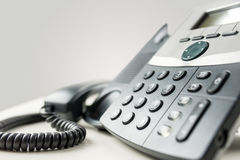 Landline telephone instrument. Close up angled view of a landline telephone instrument with a number pad and the handset or receiver off the hook in a Stock Photo