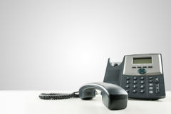 Landline telephone with the receiver off-hook. Close-up of a black business landline telephone with the receiver off-hook, on an empty desk, with copy space on Stock Images
