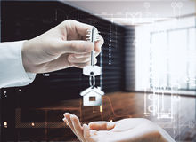 Landlord concept. Businessman handing key with house keychain to female in modern interior with daylight. Landlord concept. 3D Rendering Stock Photo