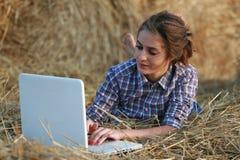 Landmädchen, das auf Heu mit Laptop liegt Lizenzfreie Stockfotos