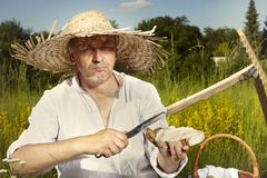 Landmann im Strohhut essend und am sonnigen Tag trinkend Stockfoto