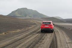LANDMANNALAUGAR, ISLANDIA - AGOSTO DE 2018: Conducción de automóviles en el campo de lava negro en el camino al área de Landmanna foto de archivo libre de regalías