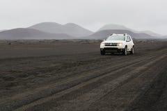 LANDMANNALAUGAR, ISLANDIA - AGOSTO DE 2018: Conducción de automóviles en el campo de lava negro en el camino al área de Landmanna fotos de archivo