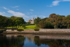 Landmark and attraction. Lews Castle in Stornoway, United Kingdom seen from sea harbor. Castle with green grounds on. Blue sky. Victorian style architecture and royalty free stock image
