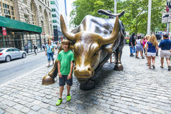 Landmark Charging Bull in Lower. NEW YORK, USA - JULY 9, 2010:  boy in front of the landmark Charging Bull in Lower Manhattan who represents strength and power Stock Photography