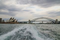 Landmark cityscape of Sydney opera house and Harbour bridge, the image was taken from the rear of the ferry in cloudy sky day. stock image