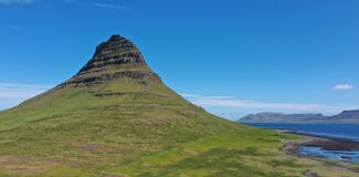 This mountain is Kirkjufell in Snaefellsnes peninsula in west Iceland.