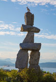 Landmark Vancouver Inukshuk sculpture seagull. Summer native americans symbol stones Inukshuk Vancouver Canada August 2017 stock photography