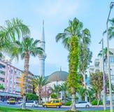 The landmarks of Ataturk boulevard in Alanya. The mosque of Hasan Senli Saray is hidden among the palms and blooming trees of Ataturk boulevard in Alanya, Turkey Stock Photography
