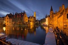 Landmarks av Bruges (Brugge) - traditionella byggnader nära bevattnakanalen, fartygen och träbryggan. Royaltyfri Fotografi