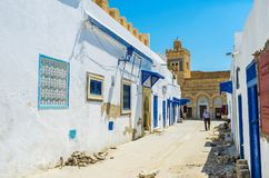The landmarks of Kairouan Medina, Tunisia. KAIROUAN, TUNISIA - AUGUST 30, 2015: The narrow street of Medina with a view on  Three Doors Mosque, decorated with Royalty Free Stock Images