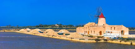 Landmarks of Sicily - salt pans and windmills in Marsala,Italy. Impressive Salt pans and traditional windmill in Marsala,Sicily,Italy royalty free stock photography