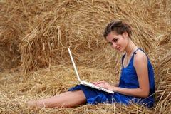Landmädchen, das auf Heu mit Laptop sitzt Lizenzfreies Stockbild