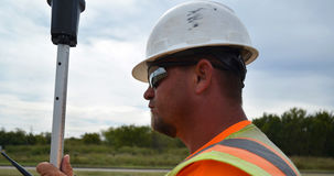 Landmeter In Safety Gear die in The Field werken stock foto's