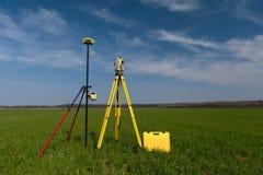Landmetersmateriaal op een driepoot op het gebied royalty-vrije stock afbeeldingen