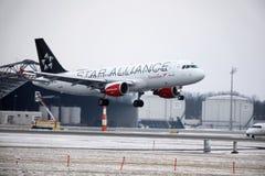 Landning för Austrian Airlines flygbuss A320-200 OE-LBZ i den Munich flygplatsen, vintertid Royaltyfria Foton