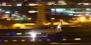 Landning för Frontier Airlines flygbuss A319-111 N908FR på natten på San Diego International Airport Arkivbild