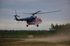 Landning för helikopter Mi-8 i moln av damm på lantligt flygfält Royaltyfria Bilder