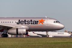 Landning för trafikflygplan för Jetstar Airways flygbuss A320 på Sydney Airport med ett Qantas flygplan i bakgrunden Arkivbild