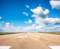 Landningsbana start- och landningsbana i flygplatsterminalen med markeringen på blå himmel med molnbakgrund Loppflygbegrepp Fotografering för Bildbyråer