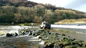 Landrover 4x4 OffRoading across lopwell Dam .Devon. A Off Roader 4x4 landrover going greenlaning across lopwell Dam., Dartmoor Devon crossing the river Tavy royalty free stock image
