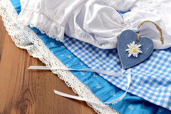 Landry pile of oktoberfest dirndle and shirt. Landry pile of blue white oktoberfest dirndle and shirt. getting dressed. wooden hearts Royalty Free Stock Photography