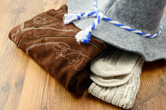 Landry pile of oktoberfest leather pants and felt hat.  Stock Photos
