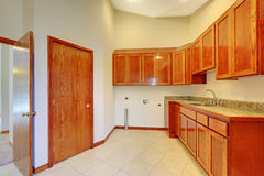 Landry room with maple custom build cabinets. Large room with build in cabinet and white Stock Photos