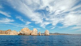 Lands End under cirrus clouds as seen from the Pacific Ocean at Cabo San Lucas in Baja California Mexico. Lands End as seen from the Pacific Ocean at Cabo San Royalty Free Stock Photos