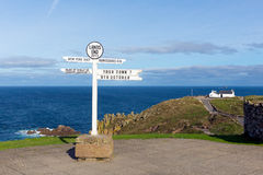 Lands End Cornwall England UK signpost blue sea and sky. Signpost at Lands End Cornwall the most westerly point of England on the Penwith peninsula eight miles Royalty Free Stock Photo
