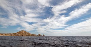 Lands End under cirrus clouds as seen from the Pacific Ocean at Cabo San Lucas in Baja California Mexico. Lands End as seen from the Pacific Ocean at Cabo San Stock Images