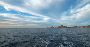Lands End under cirrus cumulus clouds as seen from the Sea of Cortes at Cabo San Lucas in Baja California Mexico. BCS Royalty Free Stock Photos
