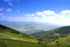 Landscape. Mountain landscape - green filed, the blue sky and white clouds Stock Photography