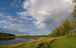 Landscape. Summer view of the river and blue sky with clouds and rainbow Royalty Free Stock Photos