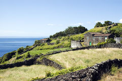 Landscape. A hilly landscape with a small house next to an ocean. Taken in Azores, Portugal Stock Photo