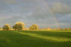 Landscape. Rural landscape before a thunderstorm with a rainbow stock photo