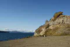 Landscape. Stone near by ocean on background of the snow mountains Stock Image