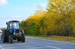 Landscape. Big tractor going on road Royalty Free Stock Image