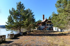Landscape with abandoned cottage with dogs and frozen lake. Stock Image