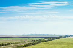 Landscape with agricultural land and industrial facilities on the horizon Stock Image
