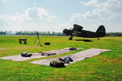 Landscape in airdrome. A fabric on a grass for packing of parachutes and the plane on a background Stock Image
