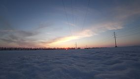 Landscape with airplane and power line on a cold sunny winter day at sunset